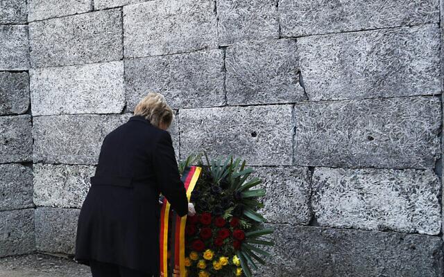 German Chancellor Angela Merkel lays down a wreath at the death wall in the former Nazi death camp of Auschwitz-Birkenau in Oswiecim, Germany, December 6, 2019. (AP Photo/Markus Schreiber)