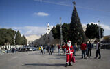 In this Dec. 5, 2019, photo, a Palestinian wearing a Santa Claus costumes welcomes Christian visitors outside the Church of the Nativity, traditionally believed by Christians to be the birthplace of Jesus Christ, in the West Bank city of Bethlehem (AP Photo/Majdi Mohammed)