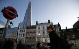 Commuters use the London underground, Wednesday, Dec. 11, 2019, backdropped by The Shard building (AP Photo/Thanassis Stavrakis)