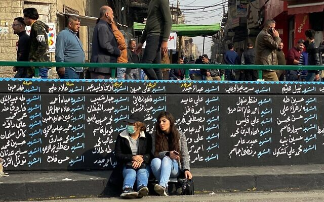 Women sit by a wall with names of nti-government protesters who have been killed in demonstrations in Tahrir Square during ongoing protests in Baghdad, Iraq, December 12, 2019. (AP Photo/Nasser Nasser)
