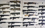 File: Semi-automatic rifles fill a wall at a gun shop in Lynnwood, Washington in October 2018 (AP Photo/Elaine Thompson, File)