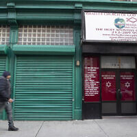 A pedestrian walks past the world headquarters of the Israelite Church of God in Jesus Christ, Thursday, Dec. 12, 2019, in the Harlem neighborhood of New York. (AP/Mary Altaffer)