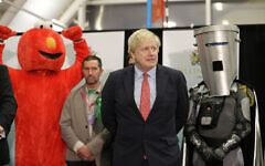 Bobby Smith, a political and fathers' rights activist and founder and leader of the 'Give Me Back Elmo' party, left, and Independent candidate Count Binface stand either side of Britain's Prime Minister and Conservative Party leader Boris Johnson wait for the Uxbridge and South Ruislip constituency count declaration at Brunel University in Uxbridge, London, Friday, Dec. 13, 2019. (AP/Kirsty Wigglesworth)