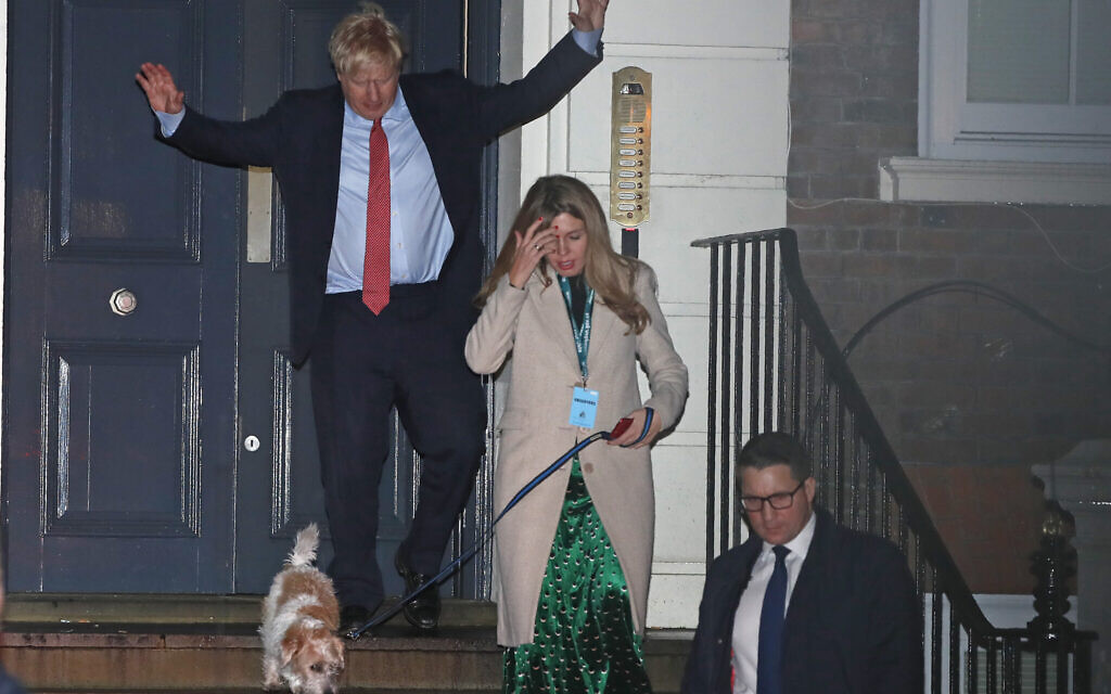 Britain's Prime Minister and Conservative Party leader Boris Johnson leaves Conservative Party headquarters with his partner Carrie Symonds and their dog Dilyn, in London, Dec. 13, 2019 (AP Photo/Thanassis Stavrakis)