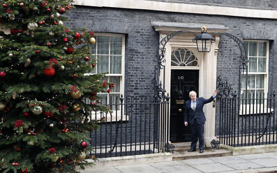 Britain's Prime Minister Boris Johnson waves as he arrives back at 10 Downing Street in London, Dec. 13, 2019 after meeting Queen Elizabeth II to seek her approval to form a new government (AP Photo/Thanassis Stavrakis)