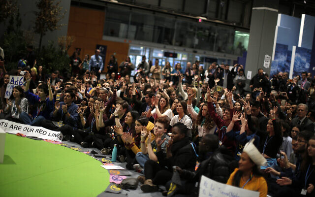 People shout slogans during a march organized by the Fridays for Future international movement of school students at the COP25 climate talks congress in Madrid, Spain, December 13, 2019. (AP Photo/Manu Fernandez)