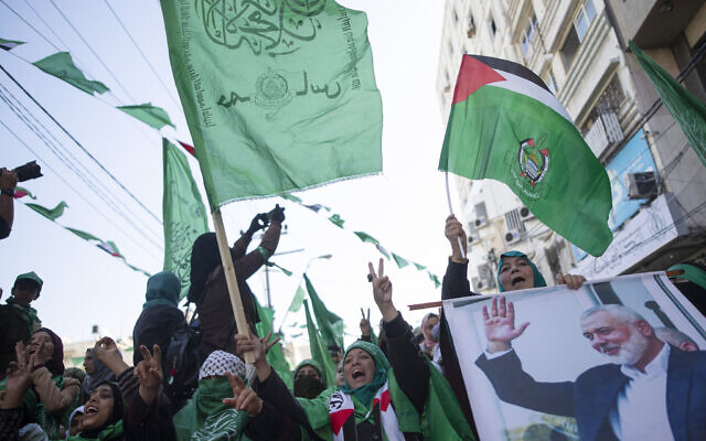 Palestinian women, one holding a picture of Hamas movement chief Ismail Haniyeh, attend a mass rally marking the 32nd anniversary of the founding of Hamas on December 14, 2019, in Gaza city. (AP/Khalil Hamra)