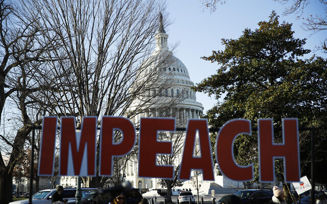 Protesters demonstrate as the House of Representatives begins debate on the articles of impeachment against US President Donald Trump at the US Capitol building, December 18, 2019, on Capitol Hill in Washington. (AP Photo/Matt Rourke)