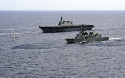 In this June 28, 2019, file photo, Japan's Maritime Self-Defense Force helicopter carrier Izumo (DDH-183) and destroyer JS Murasame (DD-101) participate in drills that included maritime navigation and emergency response exercises in Sulu Sea. (AP/Emily Wang)