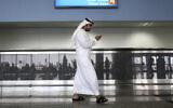 Illustrative: In this photo from October 27, 2013, a worker looks at his mobile phone at Al Maktoum International Airport in Dubai, United Arab Emirates. (Patrick Castillo/Emarat Al Youm via AP, File)