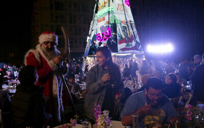 In this Monday, December 23, 2019 photo, a volunteer, center, serves drinks at a public Christmas dinner as a boy asks Santa Claus for a selfie, in Martyrs Square where anti-government activists are encamped, in Beirut, Lebanon. (AP Photo/Maya Alleruzzo)