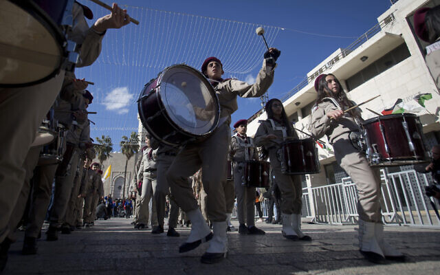 A Palestinian Scout marching band parades during Christmas celebrations outside the Church of the Nativity, built atop the site where Christians believe Jesus Christ was born, on Christmas Eve, in the West Bank City of Bethlehem, December 24, 2019. (AP Photo/Majdi Mohammed)