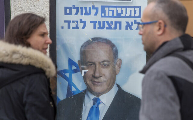 People look at a poster of Israel Prime Minister and governing Likud party leader Benjamin Netanyahu at a voting center in the northern Israeli city of Hadera, on December 26, 2019. (AP/Ariel Schalit)