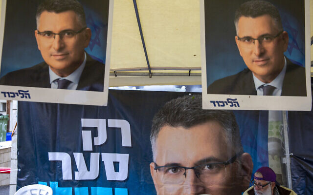 A Likud party member sits by a poster of veteran politician Gideon Saar from the governing Likud Party at a voting center in the northern Israeli city of Hadera,on December 26, 2019. (AP/Ariel Schalit)