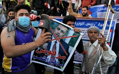"A protester hits a poster with a defaced picture of Assaad al-Aidani, the Iran-backed parliamentary bloc's nominee for the post of the prime minister, and Arabic that reads ""rejected by the people,"" with a shoe during anti-government demonstrations in Baghdad, Iraq, December 26, 2019. (AP Photo/Khalid Mohammed)"