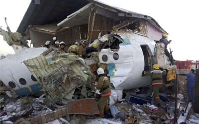 In this handout photo provided by the Emergency Situations Ministry of the Republic of Kazakhstan, police and rescuers work on the side of a plane crash near Almaty International Airport, outside Almaty, Kazakhstan, Friday, Dec. 27, 2019. ( Emergency Situations Ministry of the Republic of Kazakhstan photo via AP)