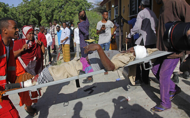 Medical personnel carry a civilian who was wounded in suicide car bomb attack at check point in Mogadishu, Somalia, December 28, 2019. (Farah Abdi Warsame/AP)