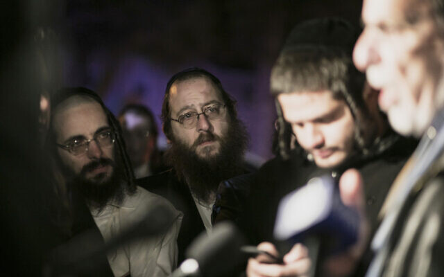 Orthodox Jews listen to ex-NY state assemblyman Dov Hikind speak in Monsey, New York, December 29, 2019, following a stabbing rampage late Saturday during a Hanukkah celebration. (AP/Allyse Pulliam)
