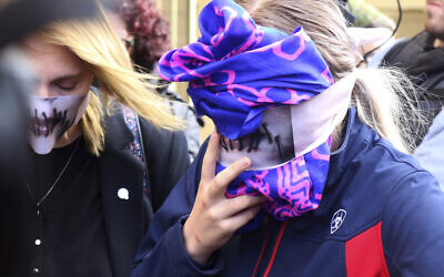 A 19-year old British woman, right, covers her face as she leaves from the Famagusta court after her trial, in Paralimni, Cyprus, Monday, Dec. 30, 2019.  (AP/Philippos Christou)