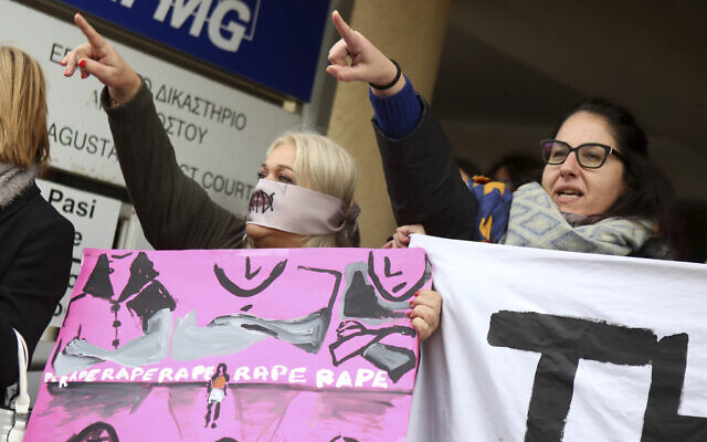 Protesters stage a demonstration outside a court house in Paralimni, Cyprus on December 30, 2019, in support of a 19 year-old British woman who was found guilty of fabricating claims that she was gang raped by 12 Israelis. (AP Photo/Philippos Christou)