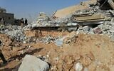 Fighters from the Kataeb Hezbollah, or Hezbollah Brigades militia, inspect the destruction of their headquarters in the aftermath of a US airstrike in Qaim, Iraq, December 30, 2019. (AP Photo)