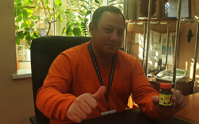 Anatoliy Kesselman shows off his brainchild, Dragon's Breath zhug, in Odessa, November 1, 2019. (Cnaan Liphshiz/JTA)
