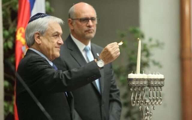 Chilean President Sebastian Pinera lights a Hanukkah candle during a ceremony on December 27, 2019, at La Moneda Palace in Santiago. (Courtesy of the Chilean government)