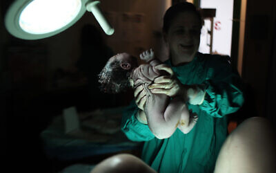 Illustrative: A nurse holds a newborn baby moments after it was delivered at the Hadassah Hospital Ein Kerem in Jerusalem, June 18, 2011. (Kobi Gideon/Flash90)