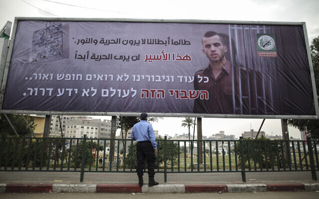 A Hamas police officer looks at a billboard in Gaza City from the terror group's military wing bearing a portrait of Israeli soldier Oron Shaul, who was killed in the 2014 Gaza war, December 29, 2017. (Wissam Nassar/Flash90)