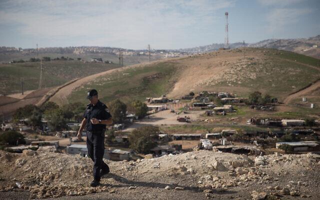 An Israeli policeman on a hilltop overlooking the West Bank Bedouin village Khan al-Ahmar on January 1, 2019. (Hadas Parush/Flash90)