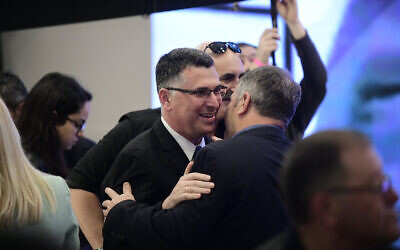 Likud MK Gideon Saar (L) embracing MK Yoav Kisch at a party conference in Ramat Gan, March 4, 2019. (Tomer Neuberg/Flash90)