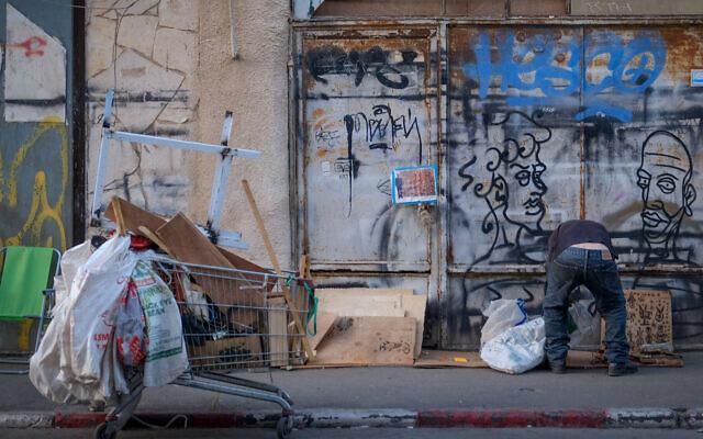 A man looks through garbage in the Florentin neighborhood of Tel Aviv. November 12, 2019 (Sara Klatt/FLASH90)