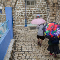 Illustrative: People walk in the rain in the northern Israeli city of Sefad, on a stormy winter day, December 9, 2019. (David Cohen/ Flash90)