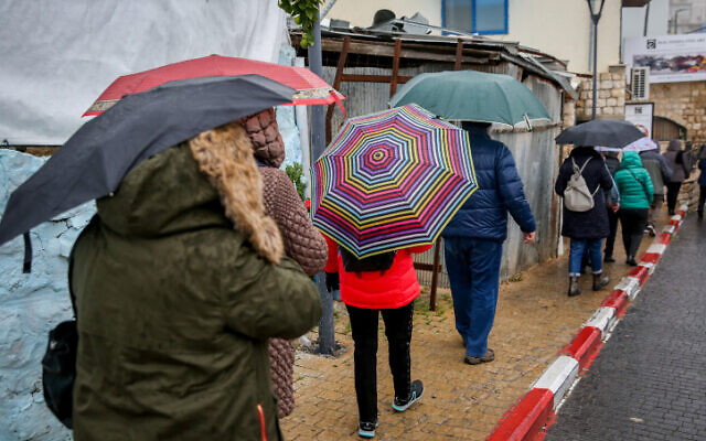 People walk in the rain in the northern Israeli city of Safed on December 9, 2019. (David Cohen/Flash90)