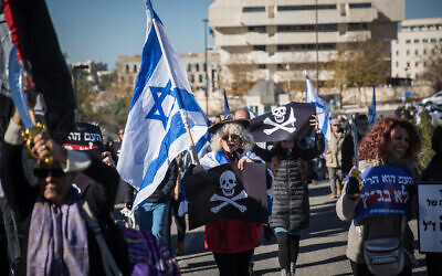 Supporters of Israeli Prime Minister Benjamin Netanyahu and activists protest against the Israeli legal system outside a court hearing at the Supreme Court in Jerusalem on whether a lawmaker facing criminal indictment can be tapped to form a coalition, December 31, 2019. (Yonatan Sindel/Flash90)