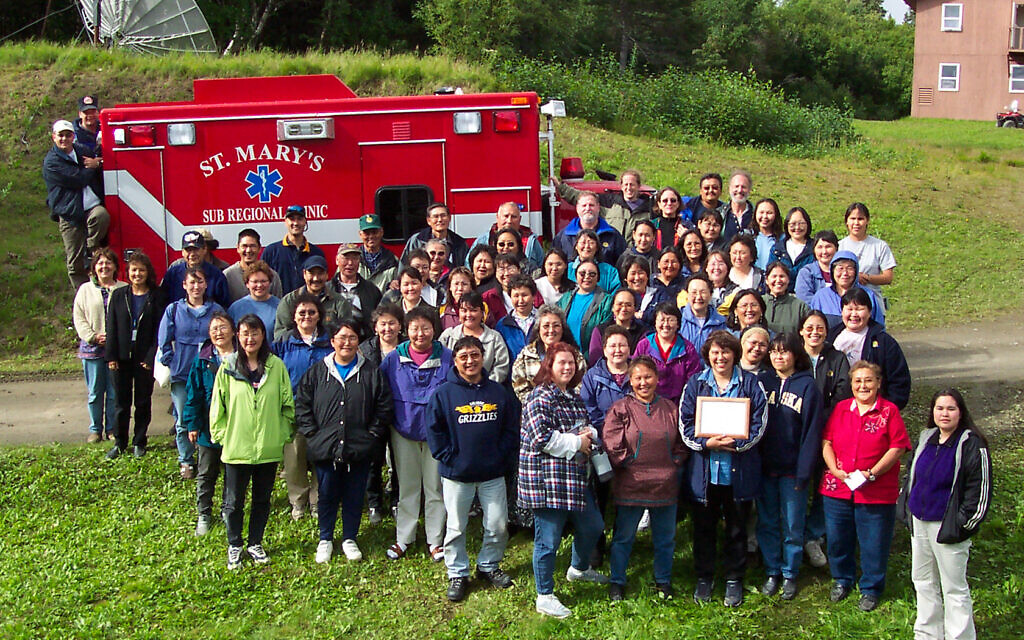 In 2003, while stationed in Alaska, Hall and her team bought an ambulance with grant money. The ambulance would serve the Village of St. Mary's. Hall is standing in the back row, hand on the ambulance. (Courtesy/ Cpt. Dana Hall)