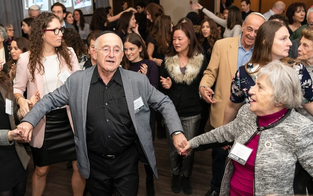Holocaust survivors join with attendees to dance the hora at the Dinner of Miracles in Toronto, December 15, 2019. (Liora Kogan)