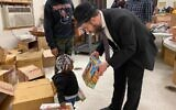 Rabbi Moshe Schapiro shows a toy to a child during the charity drive in Jersey City, New Jersey, Deember 23, 2019. (Courtesy Benny Polatseck/JTA)