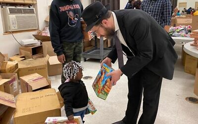 Rabbi Moshe Schapiro shows a toy to a child during the charity drive in Jersey City, N.J., Dec. 23, 2019. (Courtesy Benny Polatseck/JTA)