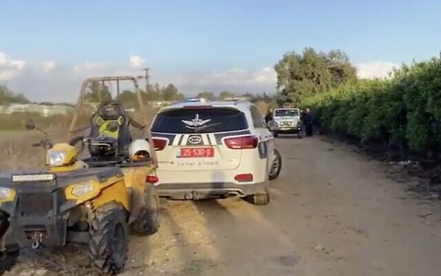 A police car and other vehicles are seen at the site where a body with gunshot wounds was found in the central city of Ramat Hasharon, December 27, 2019. (Screen capture: Twitter)