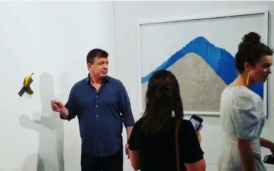 Performance artist David Datuna (L) moments before removing a $120,000 artwork -- a banana taped to a wall -- and eating it, at the Art Basel show in Miami Beach on December 8, 2019. (Screenshot: Instagram)