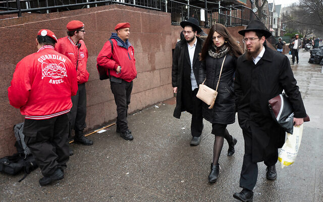Members of the Guardian Angels, left, a volunteer safety patrol organization, stand in front of the Chabad Lubavitch World Headquarters, December 30, 2019 in the Brooklyn borough of New York. (AP Photo/Mark Lennihan)