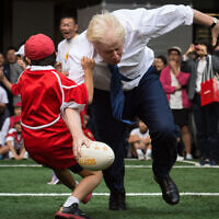 Boris Johnson takes part in a Street Rugby tournament in a Tokyo street, Oct. 15, 2015. (Stefan Rousseau/PA via AP)