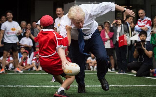 Boris Johnson takes part in a Street Rugby tournament in a Tokyo street, Oct. 15, 2015. (Stefan Rousseau/PA via AP)