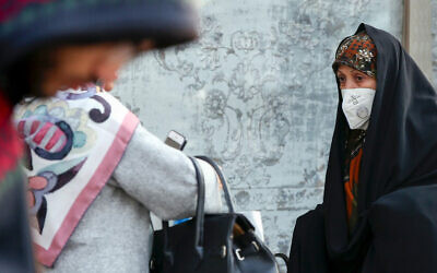 An Iranian woman wears a breathing mask due to pollution levels in Tehran, December 15, 2019. (STR/AFP)