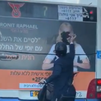 An ultra-Orthodox man vandalizing a campaign ad on a bus by tearing off the face of a woman from a poster, in footage published on December 8, 2019. (Screenshot: Twitter)