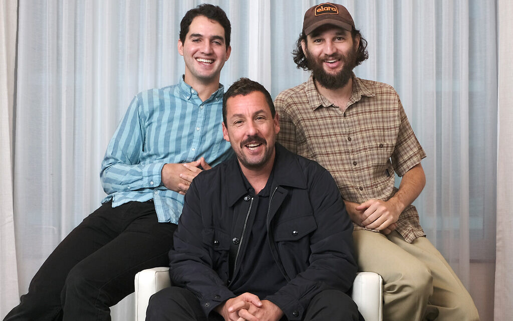 """Adam Sandler, center, star of the film """"Uncut Gems,"""" with co-directors Benny Safdie, left, and his brother Josh at the St. Regis Hotel during the Toronto International Film Festival in Toronto, Sept. 9, 2019. (Photo by Chris Pizzello/Invision/AP)"""