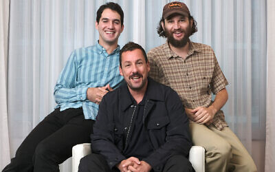 "Adam Sandler, center, star of the film ""Uncut Gems,"" with co-directors Benny Safdie, left, and his brother Josh at the St. Regis Hotel during the Toronto International Film Festival in Toronto, Sept. 9, 2019. (Photo by Chris Pizzello/Invision/AP)"