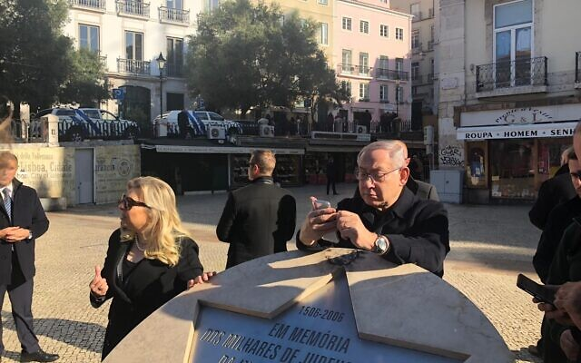 Prime Minister Benjamin Netanyahu checks a phone while leaning on a memorial to Jews massacred in Lisbon, Portugal in 1506, on December 5, 2019. (Shalom Yerushalmi/Zman Yisrael)