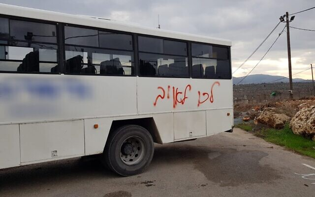 "A bus used to transport Border Police officers to the Kumi Ori outpost near Yitzhar spray-painted with the phrase ""go [join] the enemy"" on December 8, 2019. (Border Police)"